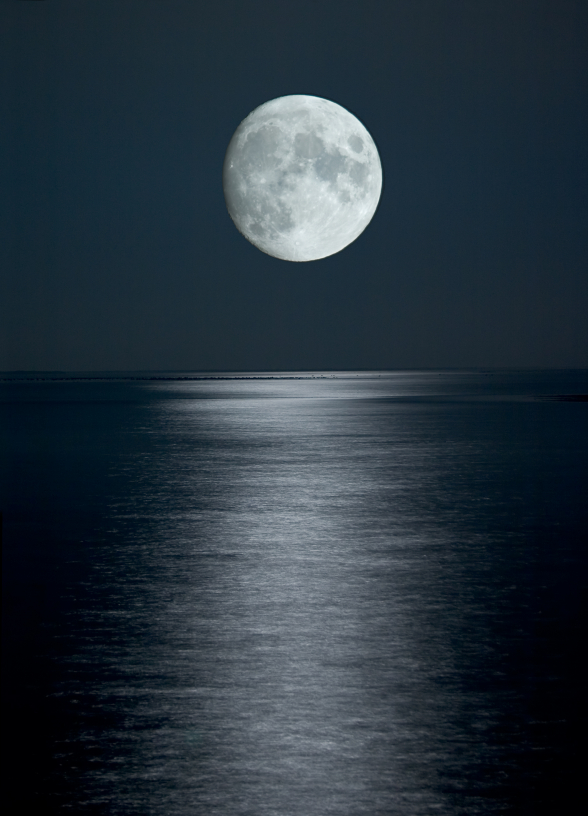 Photo of full moon in black sky above the sea with reflection